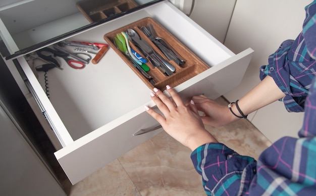 Kobieta ręce otworzyć szufladę w kuchni.