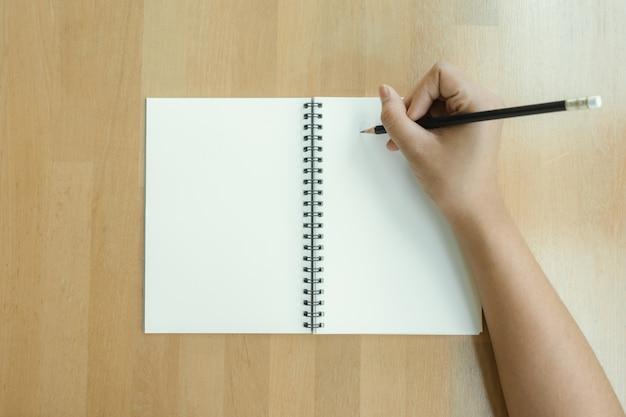 Kobieta ręce pisania na książki w biurze. business woman pracy na biurko z drewna. kobieta biznesowych pracy z komputera przenośnego i materiałów biurowych na widok z góry. skopiuj miejsce. obrazy stylu efektów klasycznych.
