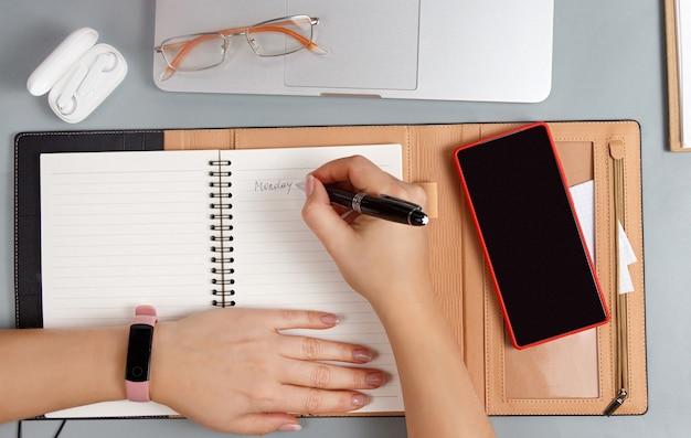 Kobieta ręce pisząc poniedziałek w porządku obrad na szarym biurku widok z góry