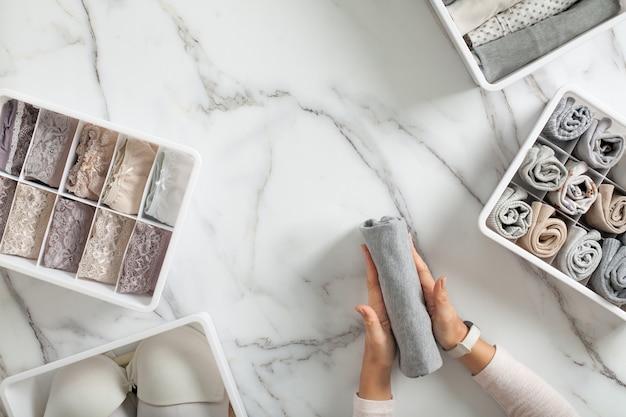Kobieta ręce starannie składane bielizny i sortuje w organizerach szuflady na białym marmurowym tle