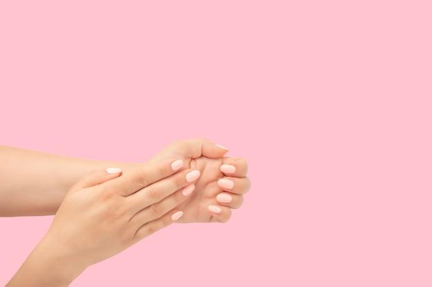 Kobieta ręce, stylowy manicure na białym tle na różowym tle, widok z góry. zbliżenie. widok z góry na pokaz kobiety upraw, pokazujący dłonie ze stylowym eleganckim manicure. szablon do reklamowania paznokci spa salorn