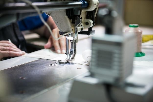 Kobieta ręce szyje ubrania wykonane z tkaniny na maszynie do szycia. ręce kobiety za pomocą maszyny do szycia. przemysł odzieżowy.