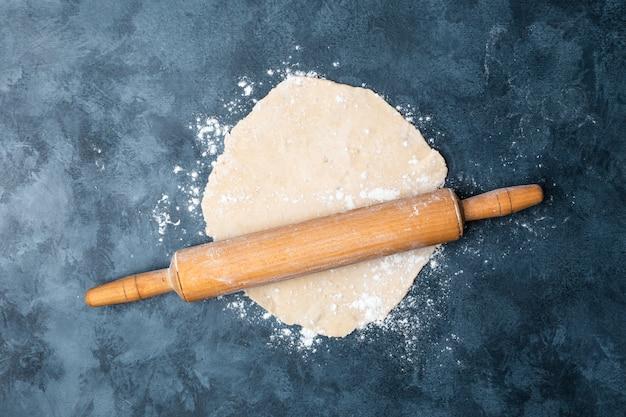 Kobieta ręce toczenia ciasta na stole z drewnianym wałkiem.