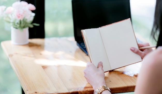 Kobieta ręce trzyma książkę, siedząc przy biurku.