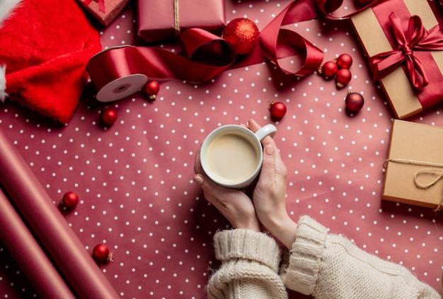 Kobieta ręce trzymać filiżankę kawy w pobliżu prezentów na papierze do pakowania
