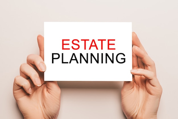Kobieta ręce trzymać papier karty z tekstem planowanie nieruchomości na powierzchni. koncepcja biznesu i finansów