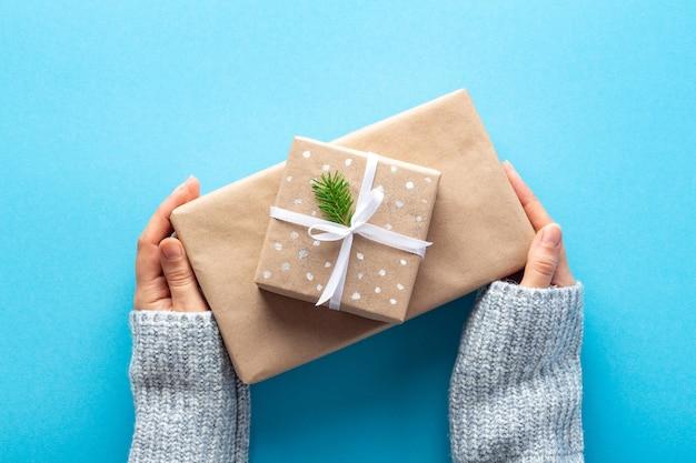 Kobieta ręce trzymać prezenty na nowy rok w ekologicznym papierze do pakowania na niebiesko