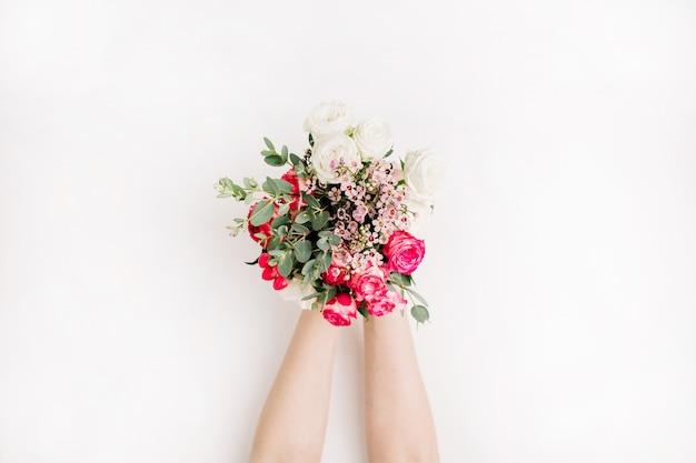 Kobieta ręce trzymają bukiet róż, gałąź eukaliptusa, polne kwiaty