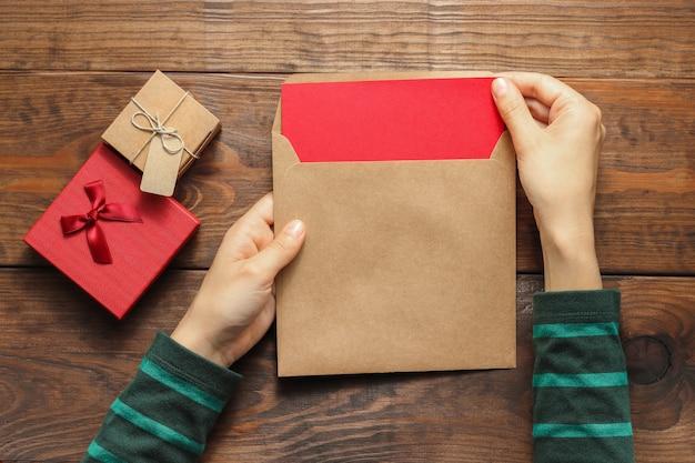 Kobieta ręce trzymają kopertę z pustą literą na drewnianym tle