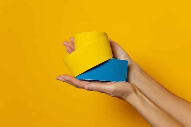Kobieta ręce trzymają rolki kinesiotape na żółtej ścianie