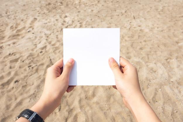Kobieta ręce trzymając biały papier z piaskiem w tle tekstury plaży.