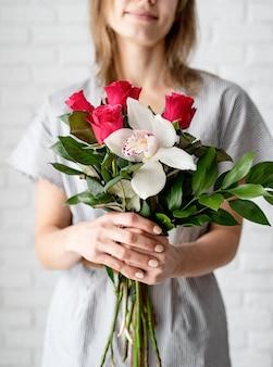 Kobieta ręce trzymając bukiet orchidei i róż obchodzi wakacje