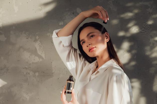 Kobieta ręce trzymając butelkę oleju do masażu lub kosmetyki do nakładania kropli na skórę twarzy. kobieta trzymać olej na tle starej ściany z cieniem z liści. koncepcja zdrowego stylu życia i samoopieki