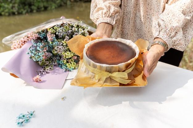 Kobieta ręce trzymając ciasto czekoladowe z bukietem kwiatów na stole.