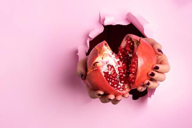 Kobieta ręce trzymając owoc granatu dojrzałe przez rozdarty różowy papier tle. świeży sok owocowy.