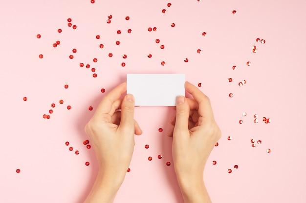 Kobieta ręce trzymając pustą kartę na różowym stole