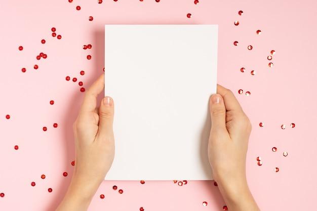 Kobieta ręce trzymając pusty arkusz papieru na różowym stole