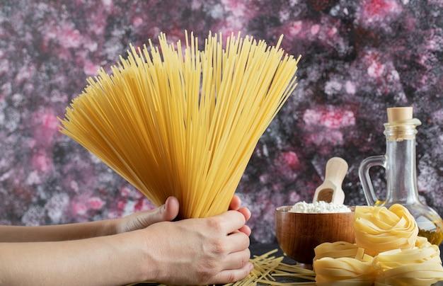 Kobieta ręce trzymając spaghetti na kolorowym tle z olejem i mąką. zdjęcie wysokiej jakości