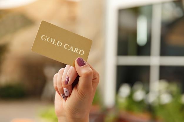 Kobieta ręce, trzymając złotą kartę
