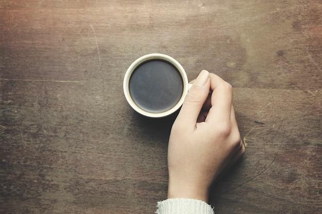 Kobieta ręce trzymające kawę na drewnianym stole