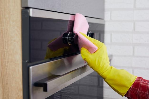Kobieta ręce w żółtych rękawiczkach do czyszczenia panelu sterowania piekarnika z różową szmatką w kuchni.