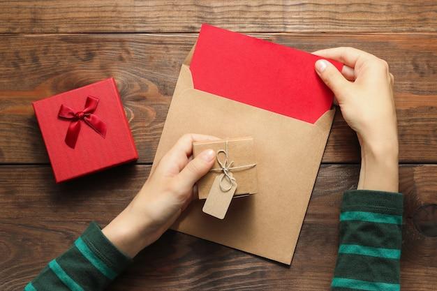 Kobieta ręce wyjmują list z koperty trzymającej pudełko na brązowym drewnianym stole w tle