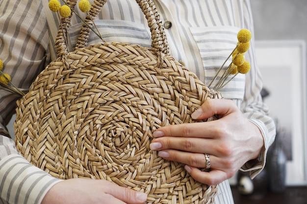 Kobieta ręce z modną stylową torbą z rattanu nago i słomianą torbą. stylowe szczegóły moda młoda kobieta.