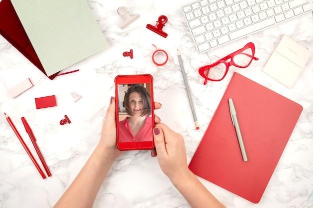 Kobieta ręce z pone z wideokonferencją. koncepcja sieci komunikacyjnej. edukacja online, ściana technologiczna. biznes online, biuro w domu, koncepcja blogu informacyjnego. widok z góry.