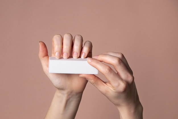Kobieta ręce z produktu do pielęgnacji paznokci
