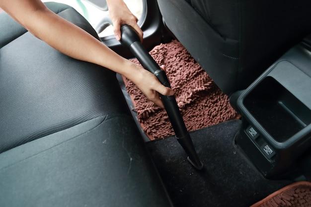Kobieta ręce za pomocą odkurzacza wnętrza samochodu