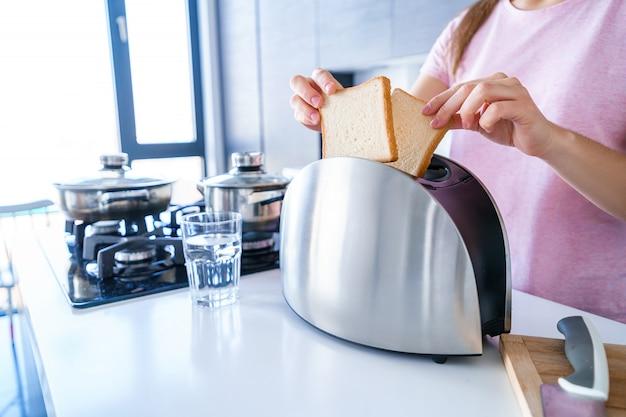 Kobieta ręce za pomocą tostera do robienia tostów śniadaniowych w kuchni. urządzenia domowe i kuchenne do gotowania żywności