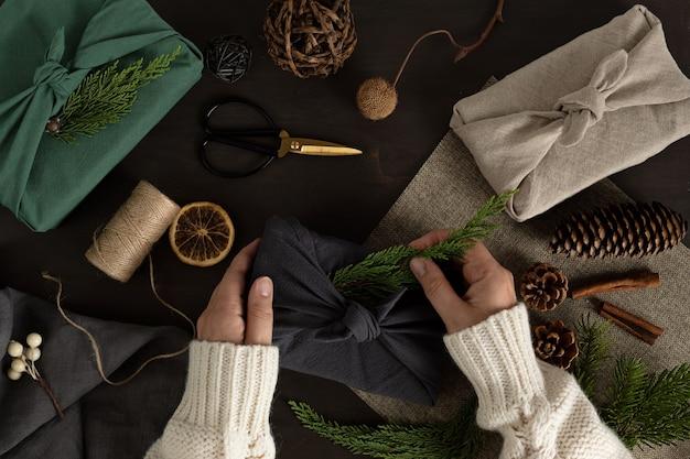 Kobieta ręce zawijające prezenty furoshiki przyjazne dla środowiska alternatywne zielone prezenty świąteczne