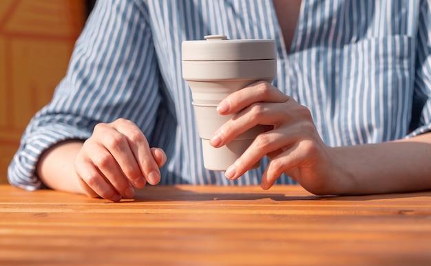 Kobieta ręce zbliżenie trzymając krzemowy kubek kawy na wynos wielokrotnego użytku w rękach nad drewnianym stołem