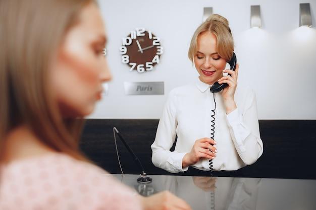 Kobieta recepcjonistka w hotelu rozmawia przez telefon w pracy z bliska
