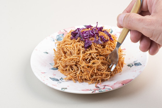 Kobieta ręcznie biorąc spaghetti z talerza widelcem