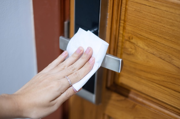 Kobieta ręcznie czyści cyfrową klamkę drzwi za pomocą mokrej chusteczki, koronawirusa ochronnego lub choroby wirusowej corona (covid-19) w domu. czysta powierzchnia, antyseptyk, styl życia, higiena i nowa normalna koncepcja
