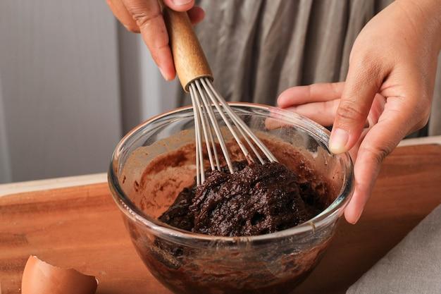 Kobieta ręcznie mieszana ciasto czekoladowe na przezroczystej misce z balonem trzepaczka krok po kroku przygotowanie do pieczenia w kuchni, robienie ciasta czekoladowego lub ciastek