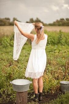 Kobieta ręcznie mycie i odkładanie prania na zewnątrz