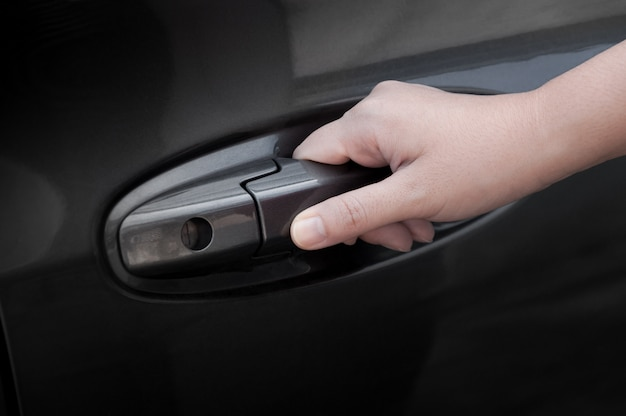 Kobieta ręcznie otworzyć drzwi samochodu, ręka ciągnąc klamkę samochodu
