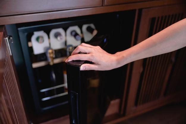 Kobieta ręcznie otworzyć przechowywanie butelek wina w lodówce. wino chłodzące i konserwujące.