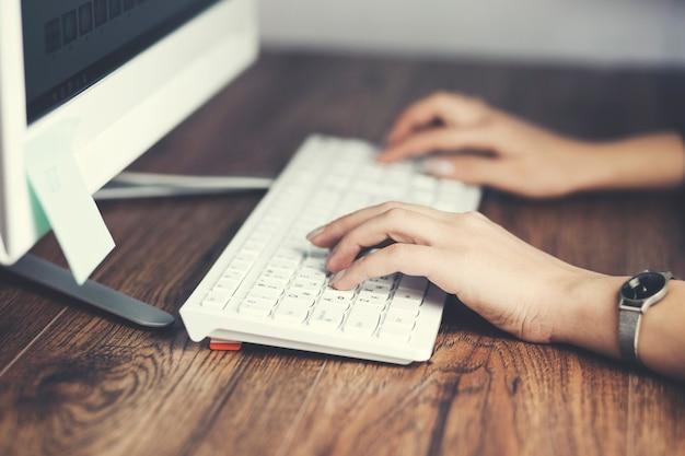 Kobieta ręcznie pisząca na klawiaturze komputera stacjonarnego