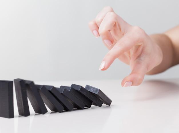 Kobieta ręcznie przewracając domino. koncepcja biznesowa reakcji łańcuchowej premium zdjęcia