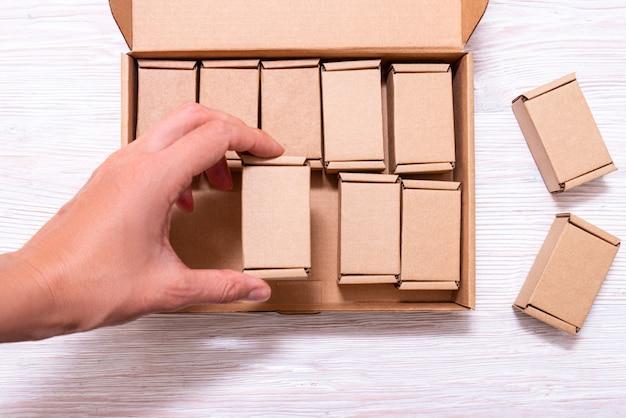 Kobieta ręcznie stawiając wiele małych kartonów wewnątrz dużej skrzynki z pokrywą