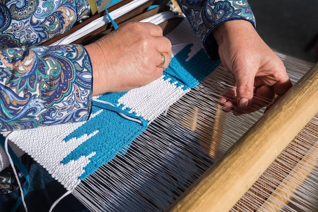 Kobieta ręcznie tkanie na ręcznym krośnie. proces tkania tkaniny w zabytkowej maszynie tkackiej.