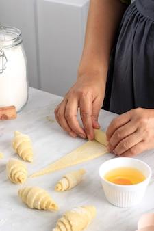 Kobieta ręcznie toczenia ciasta na bułki, proces pieczenia, co rogalik. wybrany temat, koncepcja dla piekarni