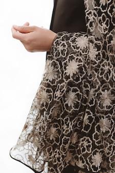 Kobieta ręcznie ubrana w złoto i czarne klasyczne ubrania z ornamentem. stylowy strzał moda. białe tło. odosobniony
