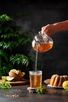 Kobieta ręcznie wylewa gorącą czarną herbatę na czarnym tle, selektywny obraz ostrości