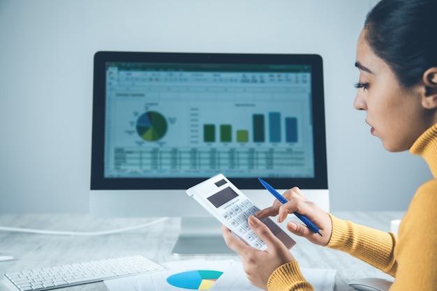 Kobieta ręczny kalkulator z komputerem w biurku