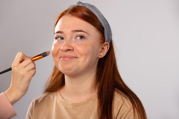 Kobieta redhaired model profesjonalny podkład z pędzelkiem kosmetycznym do makijażu koncepcji piękna na szaro