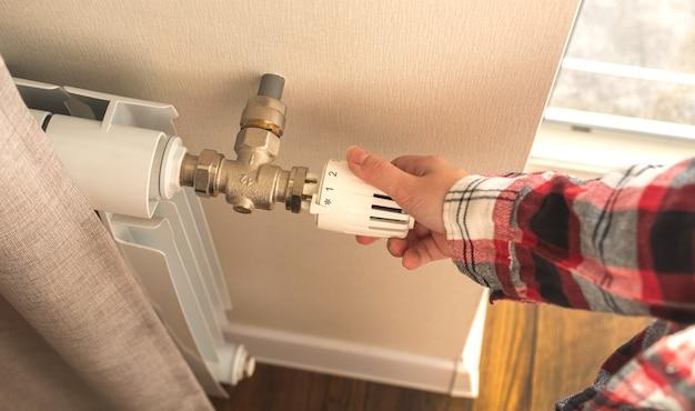 Kobieta regulująca termostat grzejnika w pomieszczeniu zdjęcie